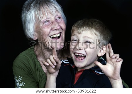 a laughing child and his grandma look happy