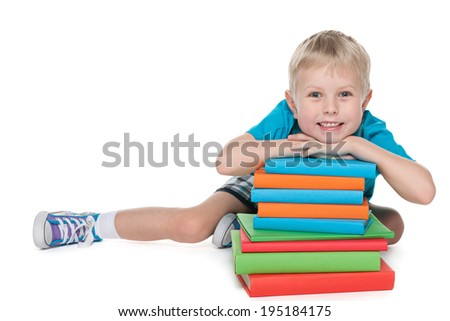 A laughing cute boy is sitting on the floor near the pile of books on the white background