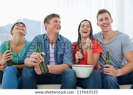 A laughing group of friends sitting with popcorn and beer as they have fun together - stock photo