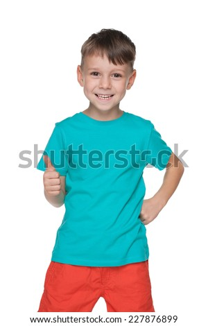 A laughing little boy holds his thumb up on the white background