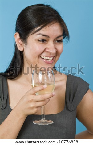 A laughing pretty young woman holding a wine glass with liquid in it. - stock photo