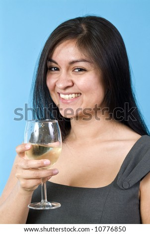 A laughing, pretty young woman holding a wine glass with liquid in it. - stock photo