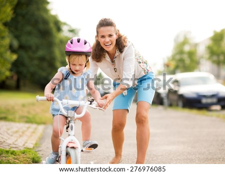 A laughing, smiling mother pushes her daughter forward on a warm summer's day as she teaches her how to ride her bicycle on a city sidewalk near a green park.  - stock photo