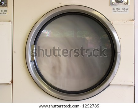 A laundromat dryer in use.  Long exposure, with motion blur on the clothes inside.