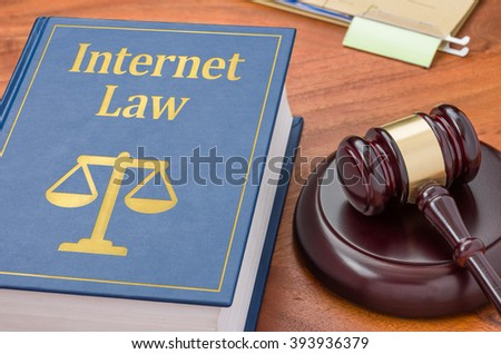 A law book with a gavel - Internet  law - stock photo