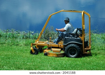 A lawnmower by the lake/pond - stock photo