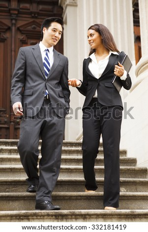 A lawyer and their client walk down the staircase of a courthouse. They are smiling and chatting. - stock photo