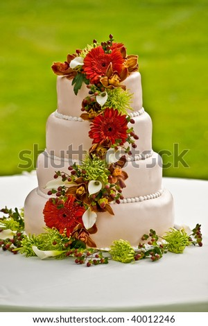 A layered and flowers decorated wedding cake - stock photo