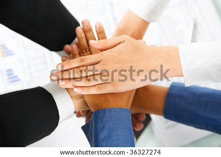 A leader hands and his employees hand in unity to express teamwork with documents on background
