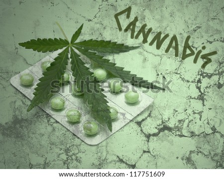 a leaf of marijuana (Cannabis sativa) on a blister with green drugs - grunge texture - stock photo
