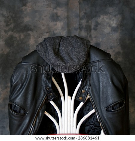 A leather biker jacket hangs on the back of a chair with a tweed cap sitting on top. - stock photo