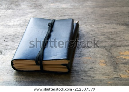 A leather bound journal sits on a table outside with a cord wrapped around the pages to keep place in book. - stock photo