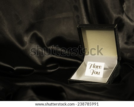 "A leather gift box opened with a note inside that has ""I love you"" written on it and a black silk sheet as a background - stock photo"