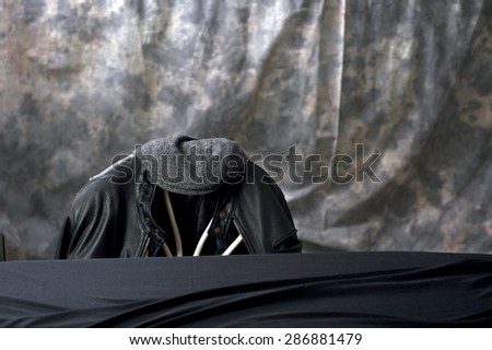 A leather motorcycle jacket hangs on the back of a chair with a tweed cap sitting on top behind a black covered table. - stock photo