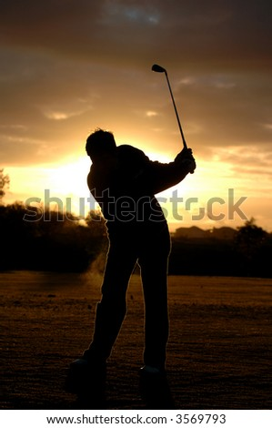 A left handed golfer practices early morning with a beautiful sunrise. - stock photo