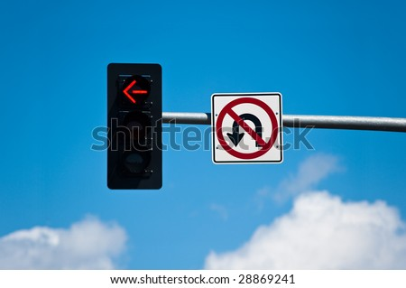 A left turn lane signal light and no u-turn sign. - stock photo