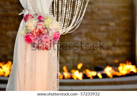 A leg of a Jewish wedding cannopy decorated with beautiful flowers with fire in the background - stock photo