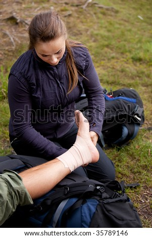 A leg tensor bandage being applied outdoors - stock photo