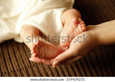 a legs one cute newborn little baby in mother's hands  - stock photo