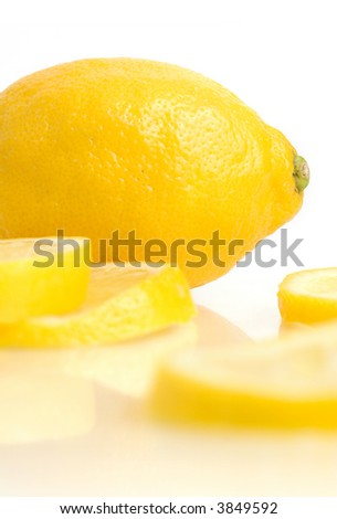 A lemon and lemon slices reflecting in white.