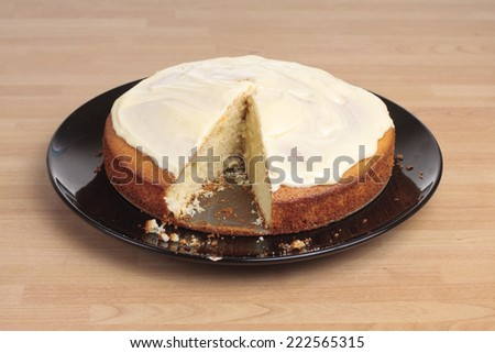 A lemon cake with icing with a slice missing - stock photo
