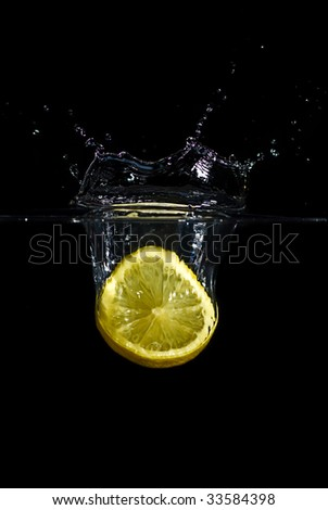 A lemon dropped into water creating a splash and bubbles. Isolated on black. - stock photo