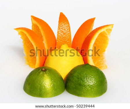 A lemon sunset, with a lemon representing the sun, orange segments as the rays and two cut lime halves as the mountains in the foreground. - stock photo