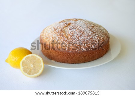 A lemon tea cake on a white plate against a white background.