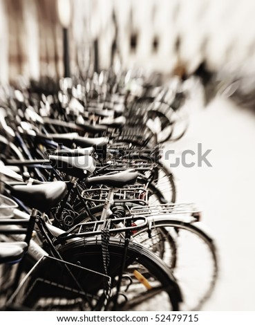A lens blurred photo of lots of parked bikes. Useful as background. - stock photo