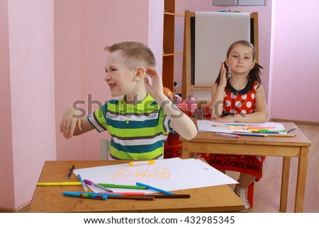 a lesson in class with a hyperactive child. hyperactive boy. the child indulges in the classroom. misbehaves. teacher talking to student. the boy waved his hands and turning his head. hyperactive boy - stock photo