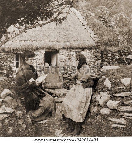 A LETTER FROM PAT IN AMERICA. Young Irish woman reading a letter from a relative in America to an older woman outside of a thatch-roofed stone cottage.