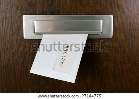 A letter in a letter box with spanish writing: Invoice - stock photo
