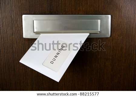 A letter in a letterbox of a door, written DUNNING