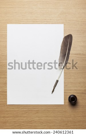 A letter paper and feather quill pen, ink on the wood desk(table), top view at the studio. - stock photo