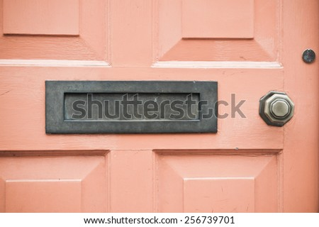 A letterbox in an orange wooden door with retro filter applied - stock photo