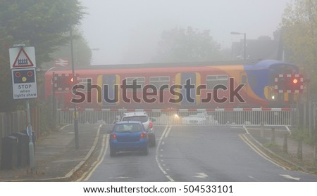 A level crossing at Motspur Park, UK, foggy day. Thick fog, impedes traffic,  occurs in great britain on about 10 days each year.