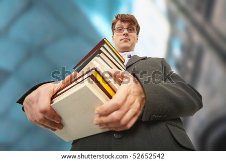 A librarian holding a big pile of books - stock photo