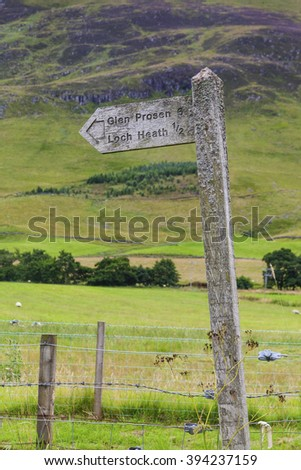 A lichen covered signpost points the way to Glen Prossen and loch Heath at Miilton of Clova, Scotland. - stock photo