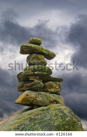 A lichen-covered stone inukshuk under an omnious sky