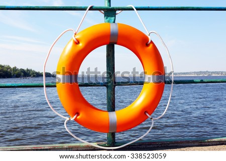 A life buoy hangs on the pier's handrail - stock photo