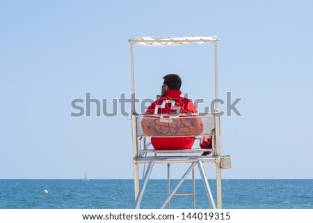 A lifeguard sitting on surveillance tower, front of the sea. / Lifeguard - stock photo