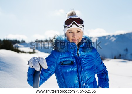 A lifestyle image of a young beautiful snowboarder standing near a slope