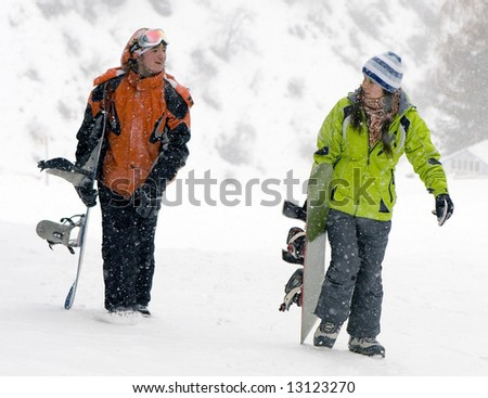 A lifestyle image of two teenagers snowboarders (series Sport, Extreme, Mountains, Horses and Teenagers) - stock photo