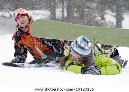A lifestyle image of two young adult  snowboarders (series Sport, Extreme, Mountains, Teenagers) - stock photo