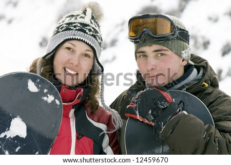 A lifestyle image of two young adult  snowboarders (series sport, mountains, extreme, horses, teenagers) - stock photo