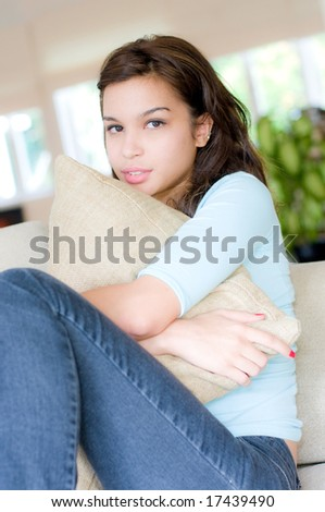 A lifestyle shot of a beautiful young woman holding a pillow