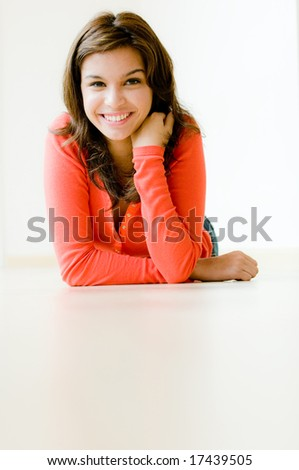 A lifestyle shot of a young woman sitting down on the floor of her modern home - stock photo