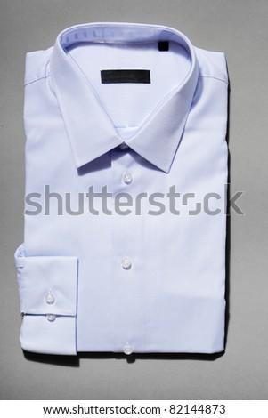 A light blue new men's dress shirt on grey background. - stock photo