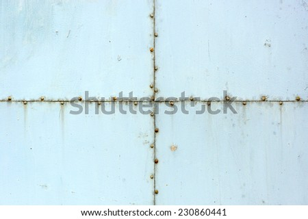 A light blue old metal background with screws - stock photo
