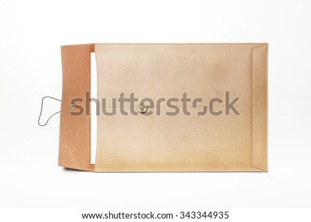 A light brown leather envelope with paper isolated white at the studio.